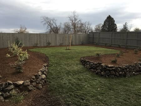 Natural rock landscaping in backyard with retaining wall