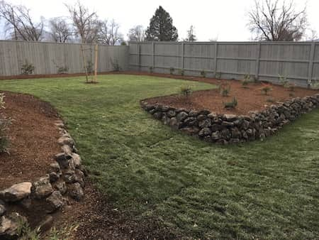 Natural rock retaining wall in backyard