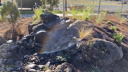 Natural rock water feature in backyard