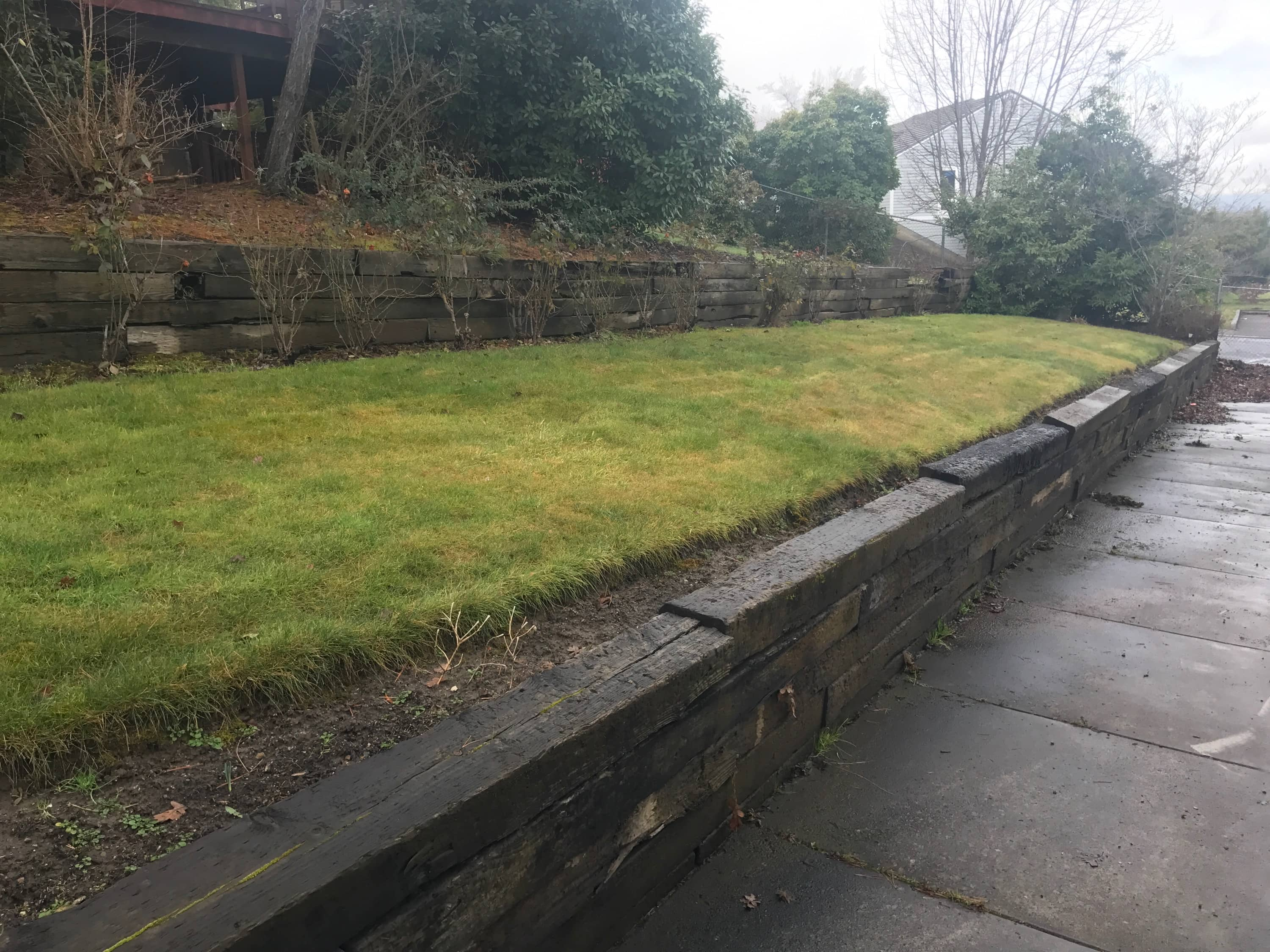 Landscaping before natural rock retaining wall
