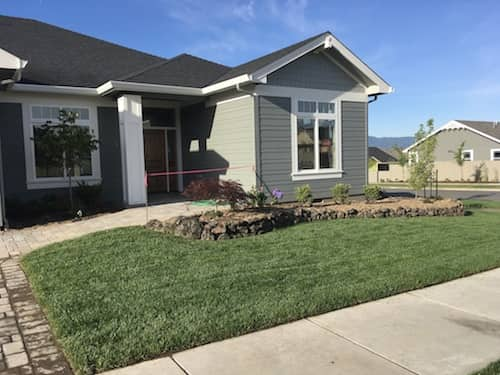 Front yard lanscaping with grass and natural rock
