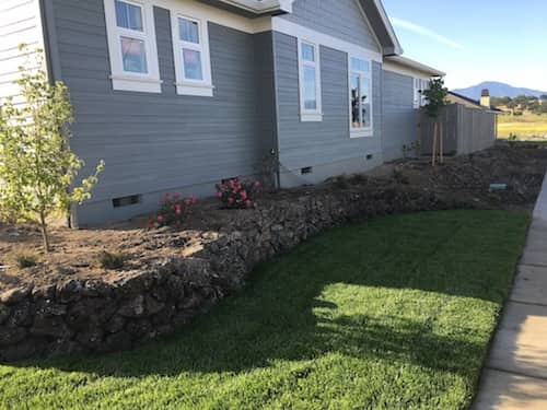 Side yard lanscaping with grass and natural rock