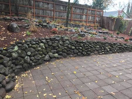 Natural Rock Wall With Brick Patio