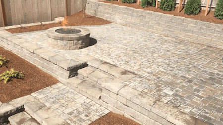 Custom paver patio with fire pit in back yard